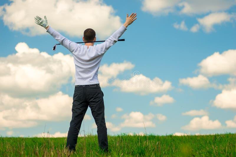 一位成功的高尔夫球运动员,在一场成功的比赛享受胜利后, 免版税库存照片