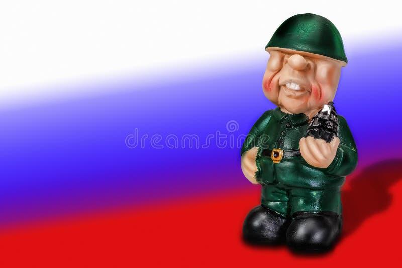 一位战士的不高兴的图制服的在与手榴弹的盔甲在手中在俄罗斯的旗子的背景 库存照片