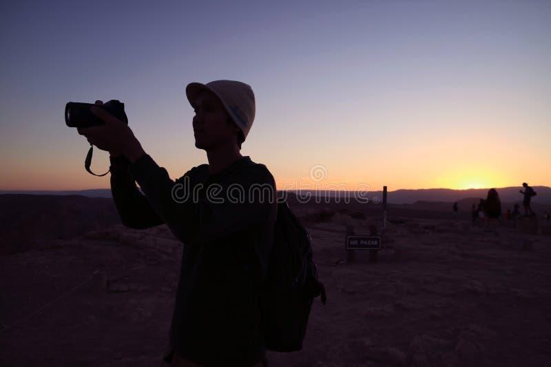 一位摄影师的剪影反对日落天空的,公告栏后边没有PASAR不意味通过 图库摄影