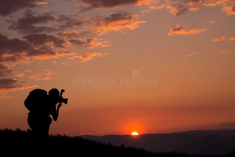 一位摄影师的剪影和美好的日落和云彩在背景中 库存图片
