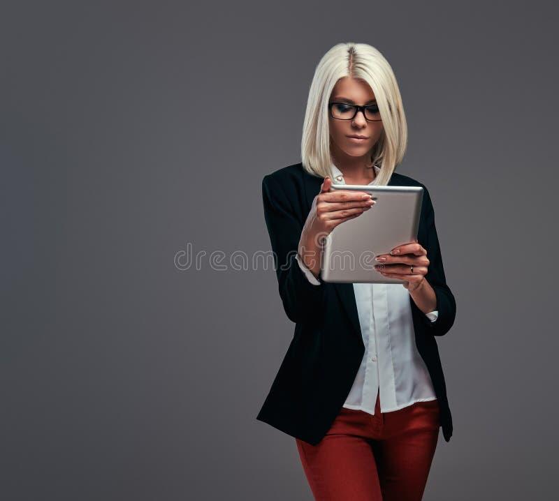 一位时兴的博客作者女性的画象现代衣裳的摆在与在灰色背景的数字式片剂 免版税库存照片