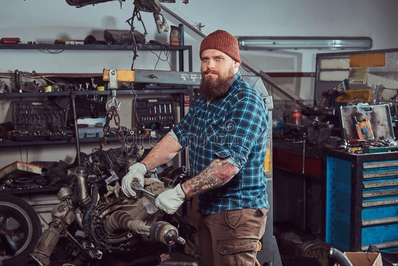 一位残酷被刺字的有胡子的技工专家修理在车库的液压悬挂被上升的发动机 图库摄影