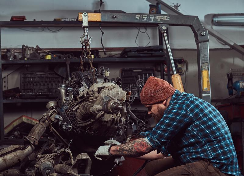 一位残酷被刺字的有胡子的技工专家修理在车库的液压悬挂被上升的发动机 免版税图库摄影