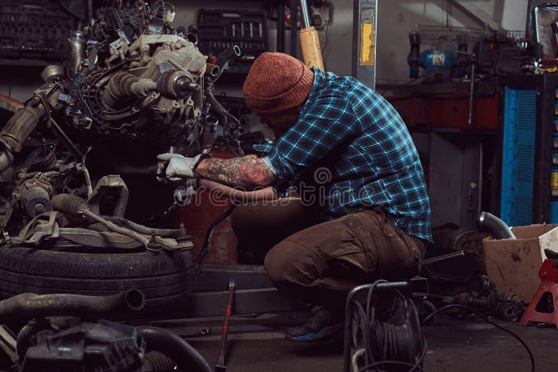 一位残酷被刺字的有胡子的技工专家修理在车库的液压悬挂被上升的发动机 免版税库存图片