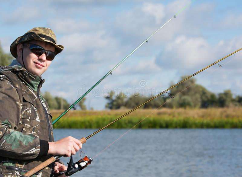 一位渔夫以抓鱼的一根实心挑料铁杆 太阳镜和渔衣裳 免版税库存照片