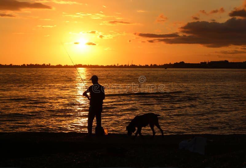 一位渔夫的剪影有一根钓鱼竿和狗的 免版税库存图片
