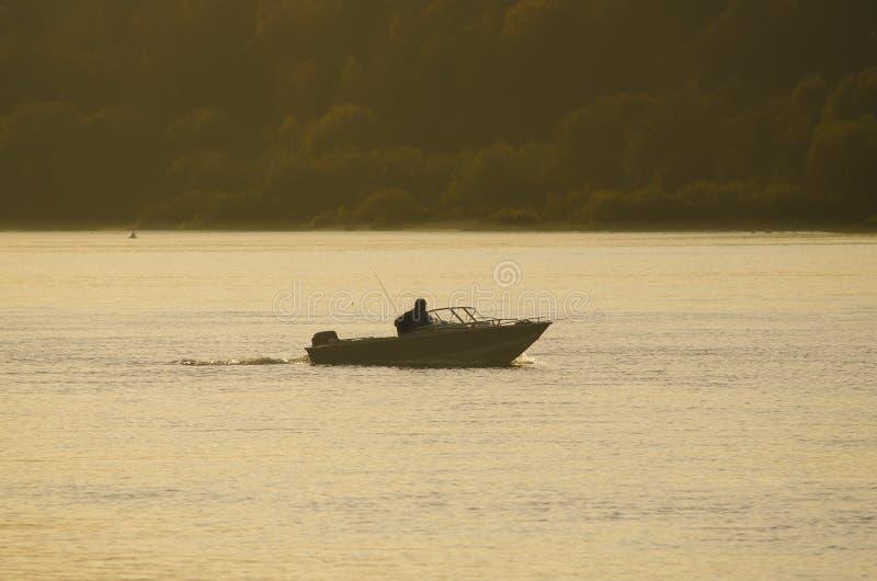 一位渔夫的无法认出的剪影小船的 库存照片