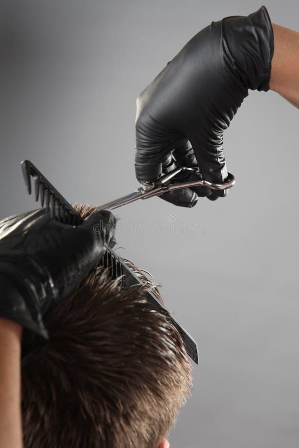 一位理发师的手手套的在工作 免版税库存图片