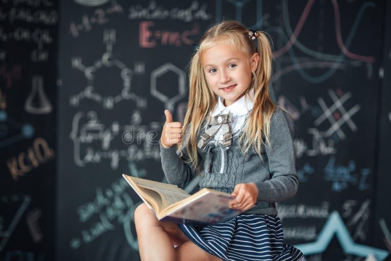 一位甜女孩女小学生坐一个黑板有学校惯例背景 工作家庭作业在读书旁边并且显示拇指 免版税库存照片