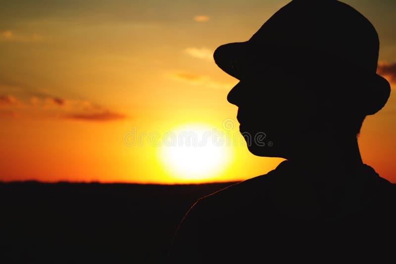 一位男性农夫的剪影帽子的在领域 库存照片