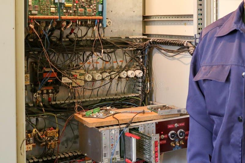 一位男性工作的电工在与导线、晶体管、保险丝、电子和开关的一个电子盘区前面站立 免版税库存照片