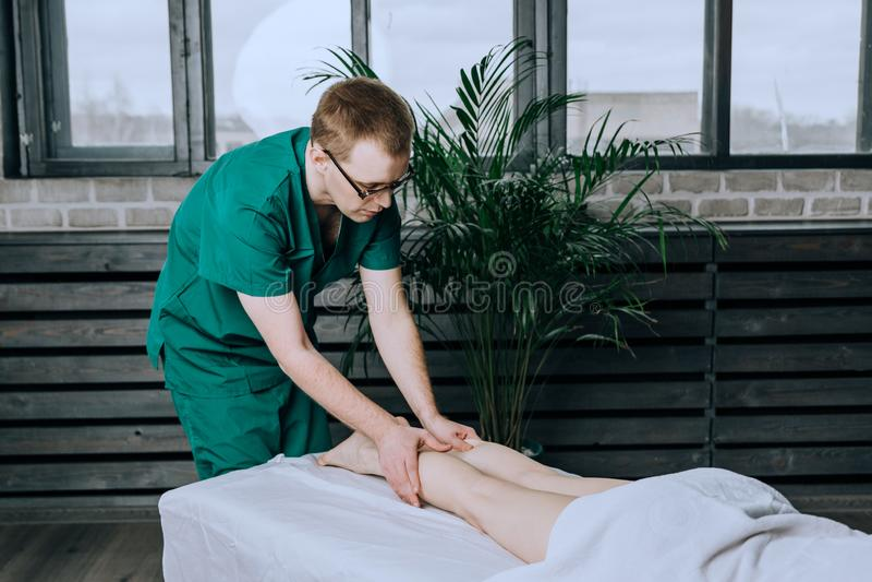 一位男性按摩治疗师按摩女性腿的脚和腿 脚小牛按摩 库存图片