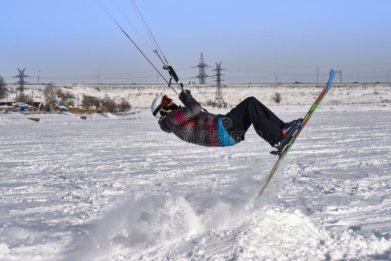 一位男性运动员参与kiting在一个大多雪的湖的冰的雪 他执行跃迁 冬天晴朗的冷淡的天 特写镜头 免版税库存图片