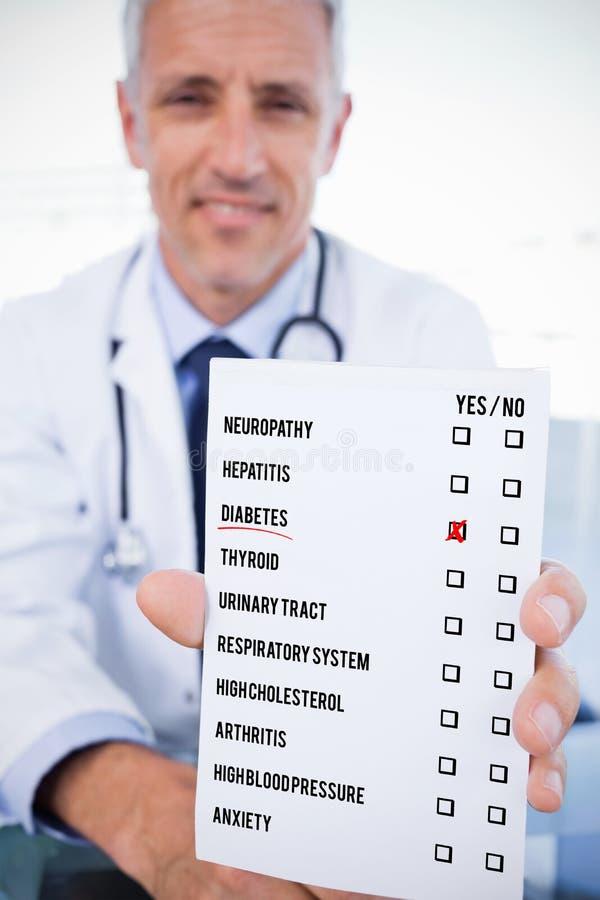 一位男性医生的画象的综合图象显示空白的处方板料的 免版税库存照片