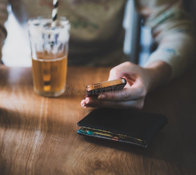 一位白女性在一个明亮的环境里坐了下来饮用的姜啤,在她的手机 免版税库存照片