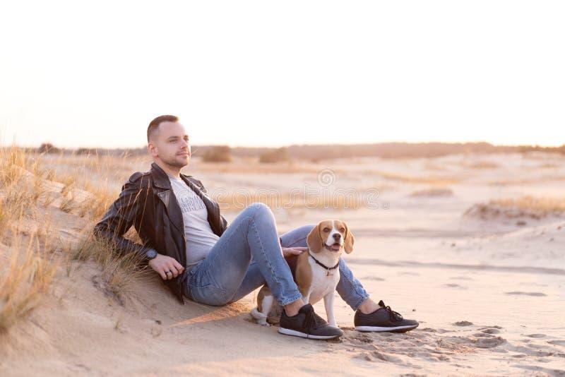 一位白种人年轻男子穿着黑色皮夹克和蓝色牛仔裤,坐在沙滩上,他的朋友比格犬旁边 免版税库存图片