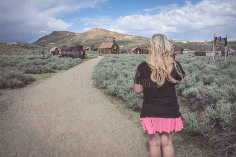一位白肤金发的女性在道路走向被放弃的大厦在Bodie加利福尼亚鬼城  免版税图库摄影