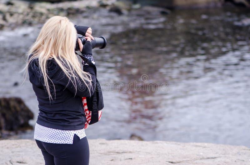 一位白肤金发的女性摄影师为大西洋照相 图库摄影