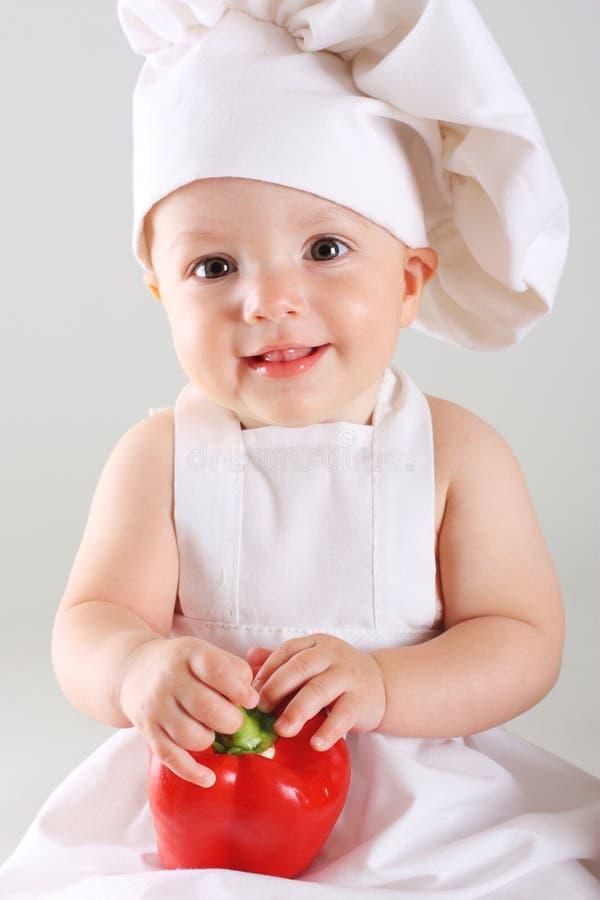 一位盖帽厨师的小婴孩用胡椒 库存照片