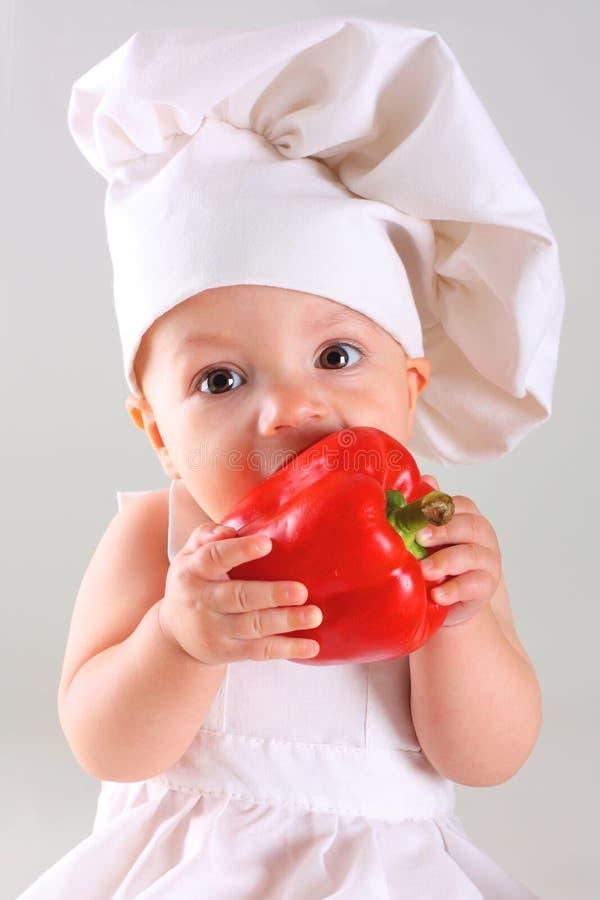 一位盖帽厨师的小婴孩用胡椒 免版税库存图片