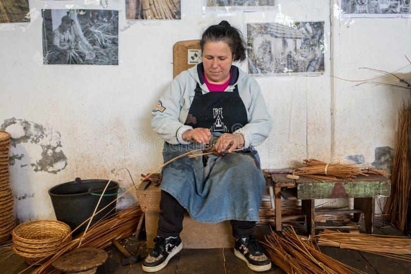 一位篮子织布工在工作在工厂商店在卡马沙在马德拉海岛,葡萄牙上 免版税库存照片