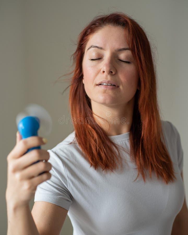 一位红发女子的画像,她手上拿着一个兜风扇 一个女孩的全脸,在风吹的酷热中提神 库存图片