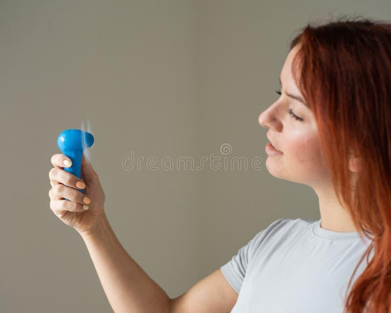 一位红发女子的画像,她手上拿着一个兜风扇 一名女孩的轮廓在酷热中被风吹得焕然一新 库存图片