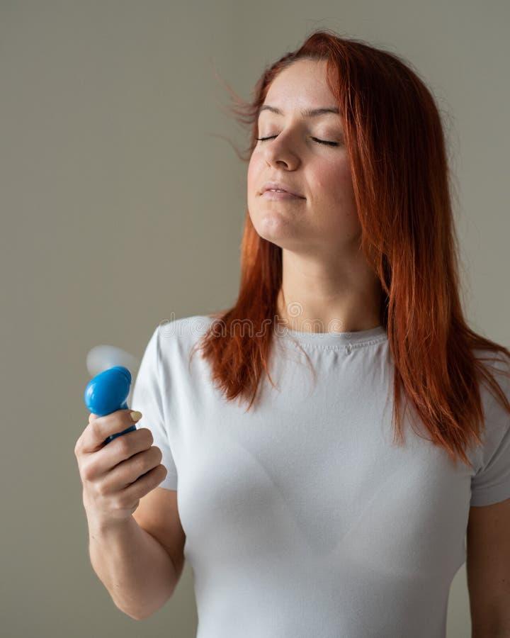 一位红发女子的画像,她手上拿着一个兜风扇 一名女孩的轮廓在酷热中被风吹得焕然一新 图库摄影