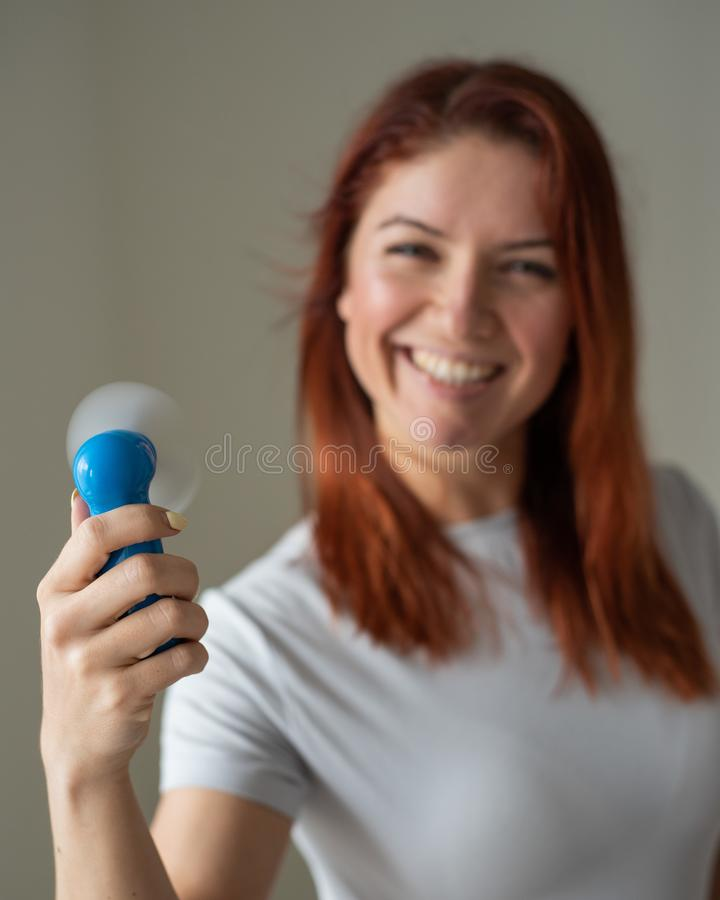 一位红发微笑的女人的画像,她手上拿着一个兜风扇 一个女孩在风中清爽的脸 库存照片