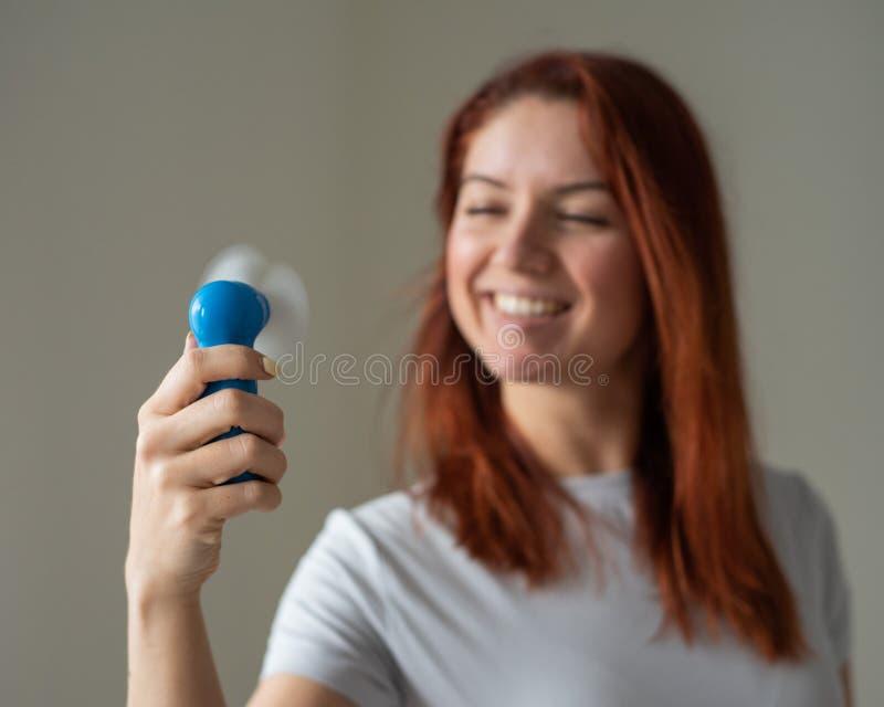 一位红发微笑的女人的画像,她手上拿着一个兜风扇 一个女孩在风中清爽的脸 库存图片
