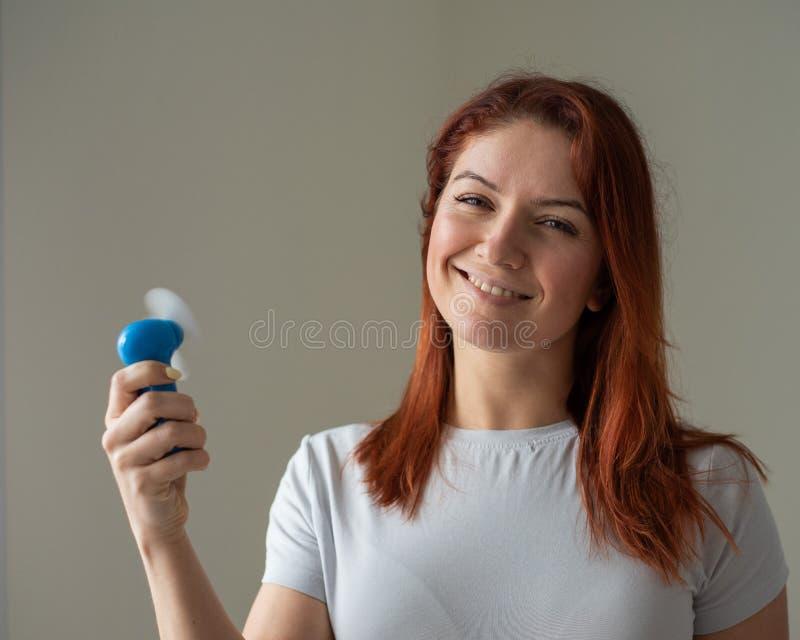一位红发微笑的女人的画像,她手上拿着一个兜风扇 一个女孩在风中清爽的脸 免版税图库摄影
