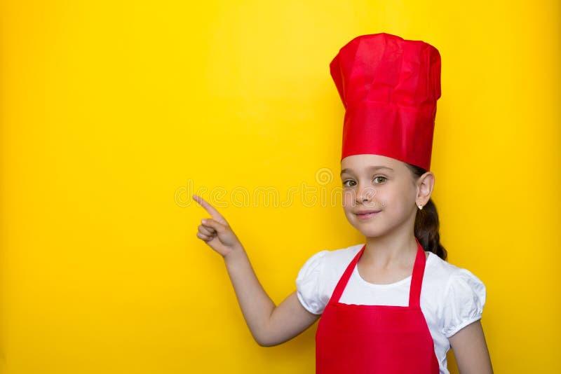 一位红色厨师的衣服点的微笑的女孩她的在空间的手指在上写字的在黄色背景 免版税库存图片
