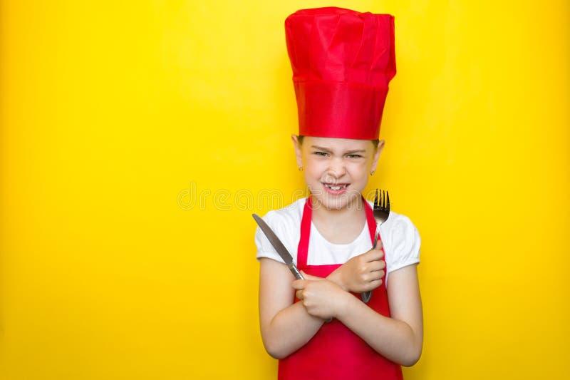 一位红色厨师的衣服藏品匙子和叉子的,胳膊恼怒的女孩在与拷贝空间的黄色背景横渡了, 免版税库存照片