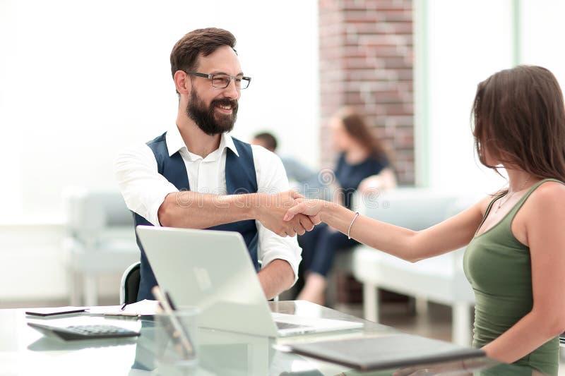 一位经理和一名顾客的握手书桌的 图库摄影