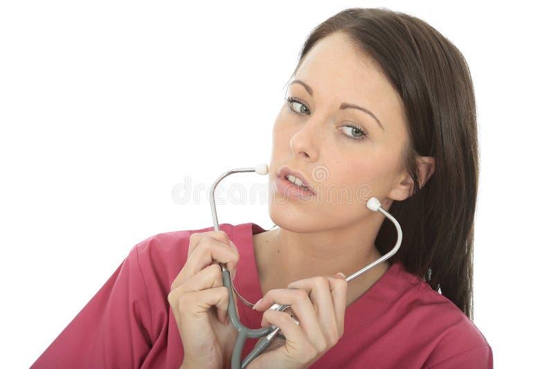 一位美丽的专业严肃的年轻女性医生Putting On A Stethoscope的画象 图库摄影