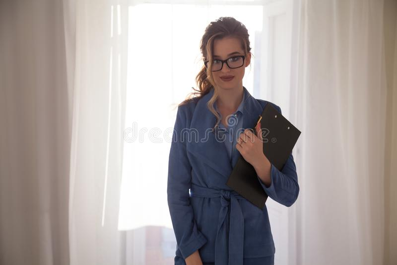一位美丽的女商人秘书的画象在办公室在电话谈判 免版税库存图片