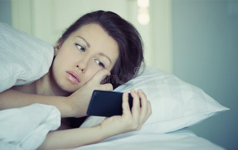 一位美丽的女性在床上在智能手机在,并且不可能睡着并且不读新闻 失眠 心理学 恐惧 免版税库存照片