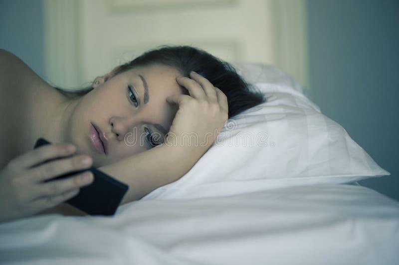一位美丽的女性在床上在智能手机在,并且不可能睡着并且不读新闻 失眠 心理学 恐惧 库存图片