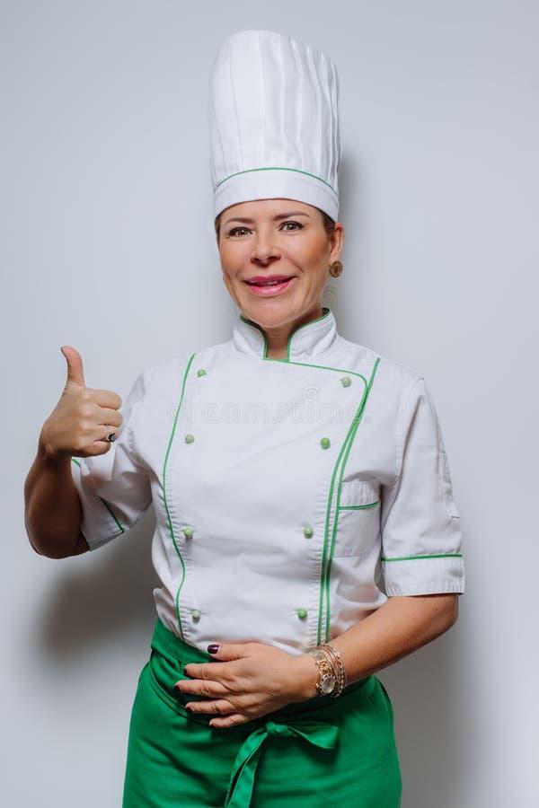 一位美丽的妇女厨师的演播室画象制服的 一件盖帽和制服的一位微笑的妇女厨师在灰色背景 免版税图库摄影