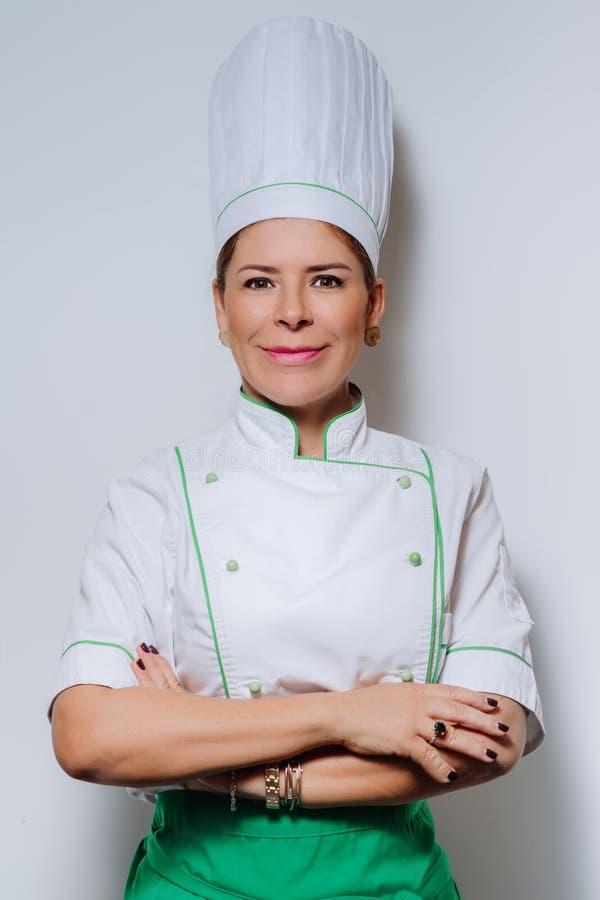 一位美丽的妇女厨师的演播室画象制服的 一件盖帽和制服的一位微笑的妇女厨师在灰色背景 免版税库存照片