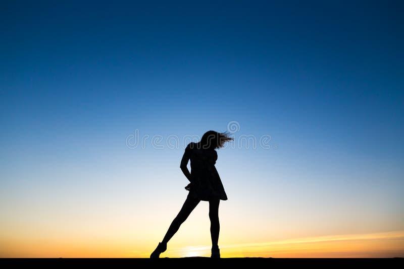 一位美丽的愉快的健康妇女舞蹈家的剪影 免版税库存照片