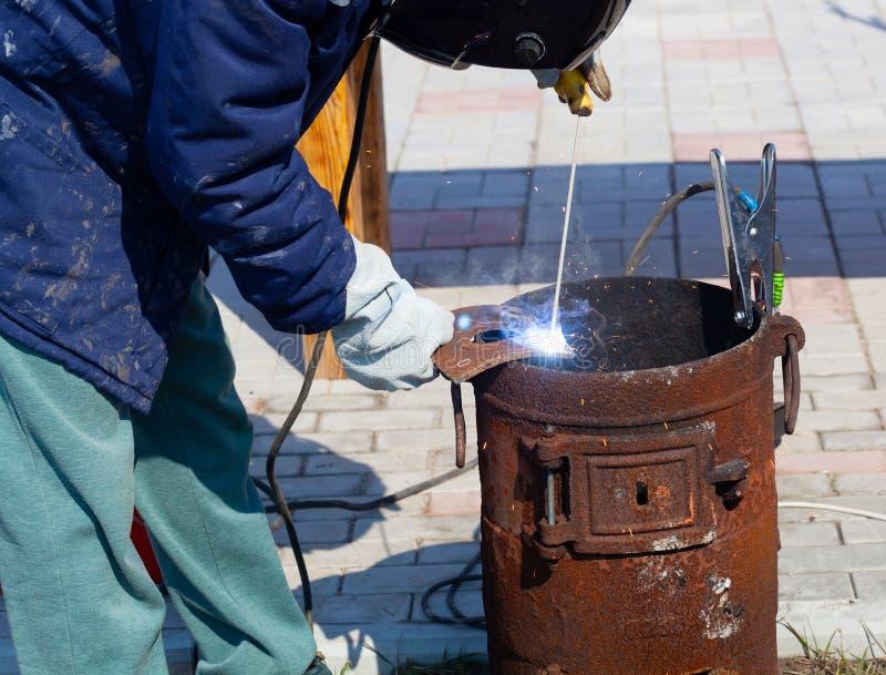一位老练的焊工在工作 生铁熔炉的准备和焊接过程 选择焦点 E 库存图片