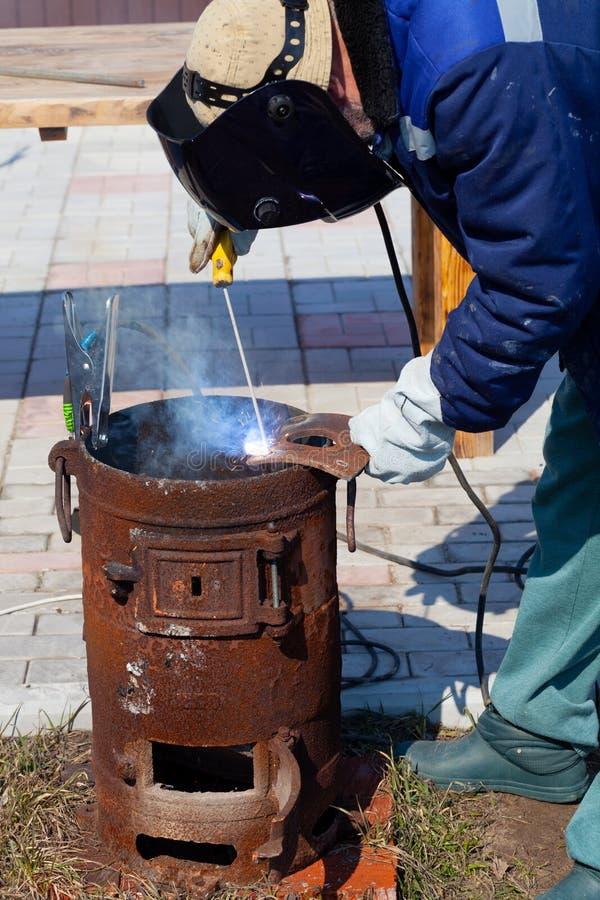 一位老练的焊工在工作 生铁熔炉的准备和焊接过程 选择焦点 E 免版税库存图片