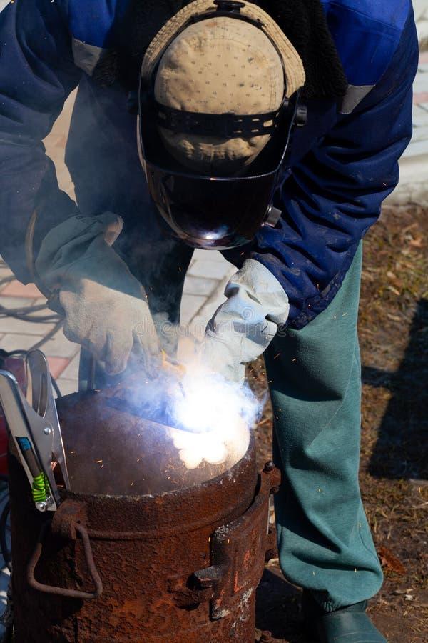 一位老练的焊工在工作 生铁熔炉的准备和焊接过程 选择焦点 E 免版税库存照片