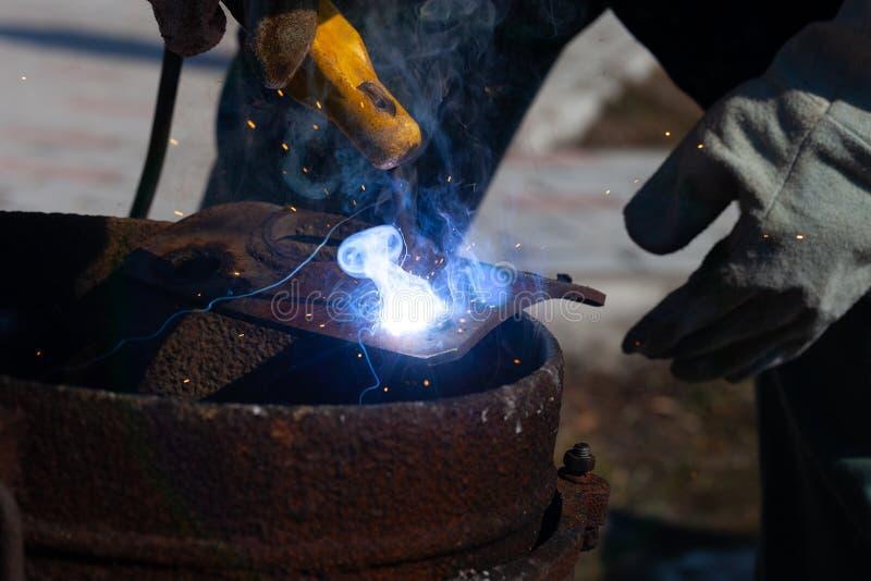 一位老练的焊工在工作 生铁熔炉的准备和焊接过程 选择焦点 E 库存照片