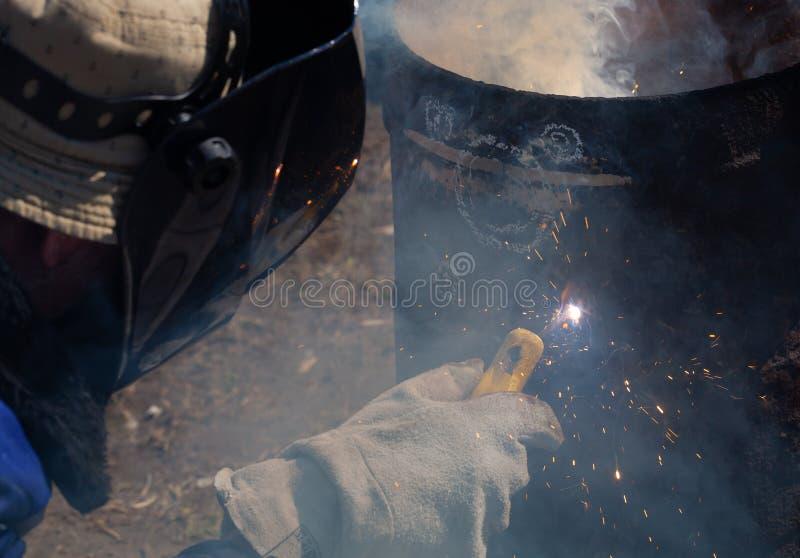 一位老练的焊工在工作 生铁熔炉的准备和焊接过程 选择焦点 E 免版税图库摄影
