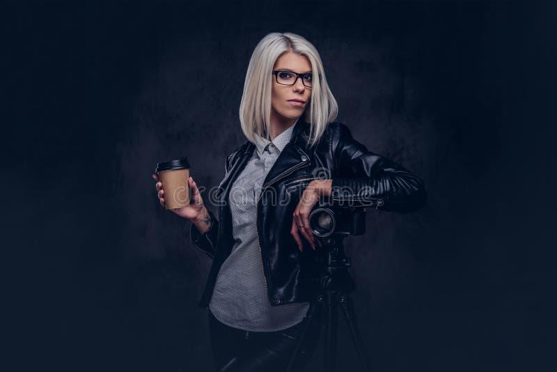 一位聪明的白肤金发的女性摄影师的画象时髦衣裳和玻璃的举行一份外带的咖啡和摆在,当时 免版税库存照片