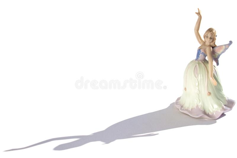 一位舞蹈家的瓷小雕象一件礼服的有翼和阴影的 库存照片