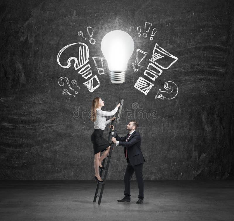 一位英俊的经理协助一个美丽的同事爬上台阶到达新的企业想法 一个电灯泡作为概念  免版税库存照片