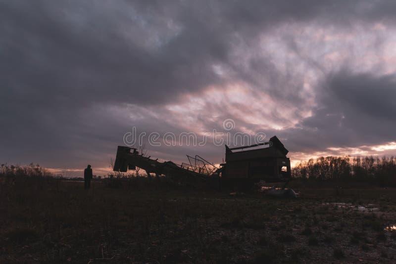 一位蒙面人物站在采石机旁,在冬日的夜晚望向日落,这是一幅阴郁、情绪化、冬季的剪辑 免版税图库摄影